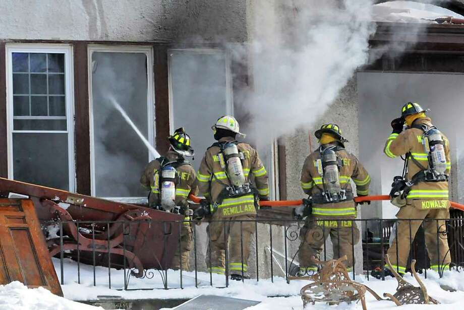 Firefighters work to put out a fire at a home on Maple Ave. in Troy, NY on Monday, February 21, 2011.  (Lori Van Buren / Times Union) Photo: Lori Van Buren
