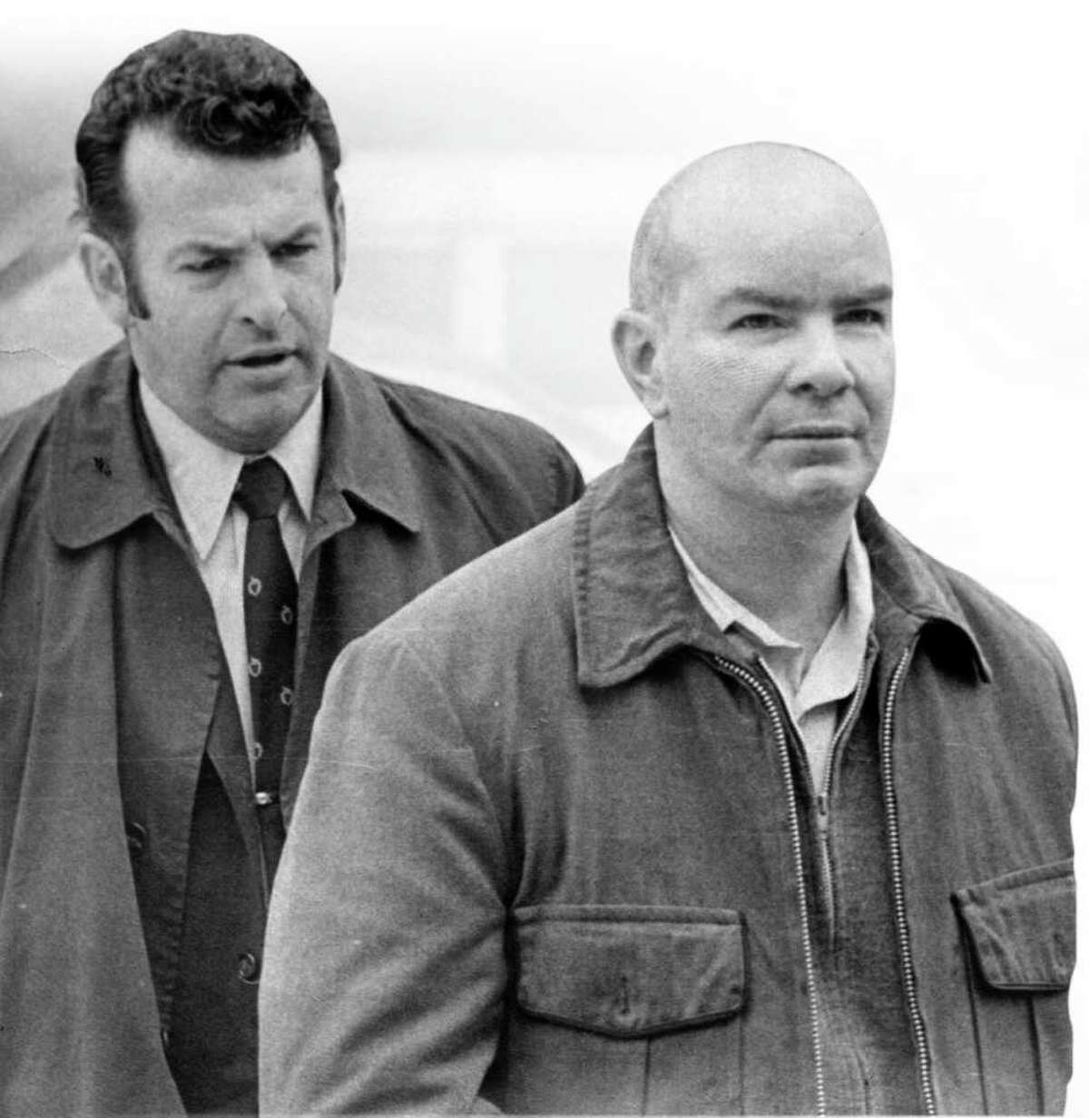 George Mayer, then a Stamford police detective, escorts Ben Miller into police headquarters on March 16, 1972, when Miller was booked on five counts of murder.