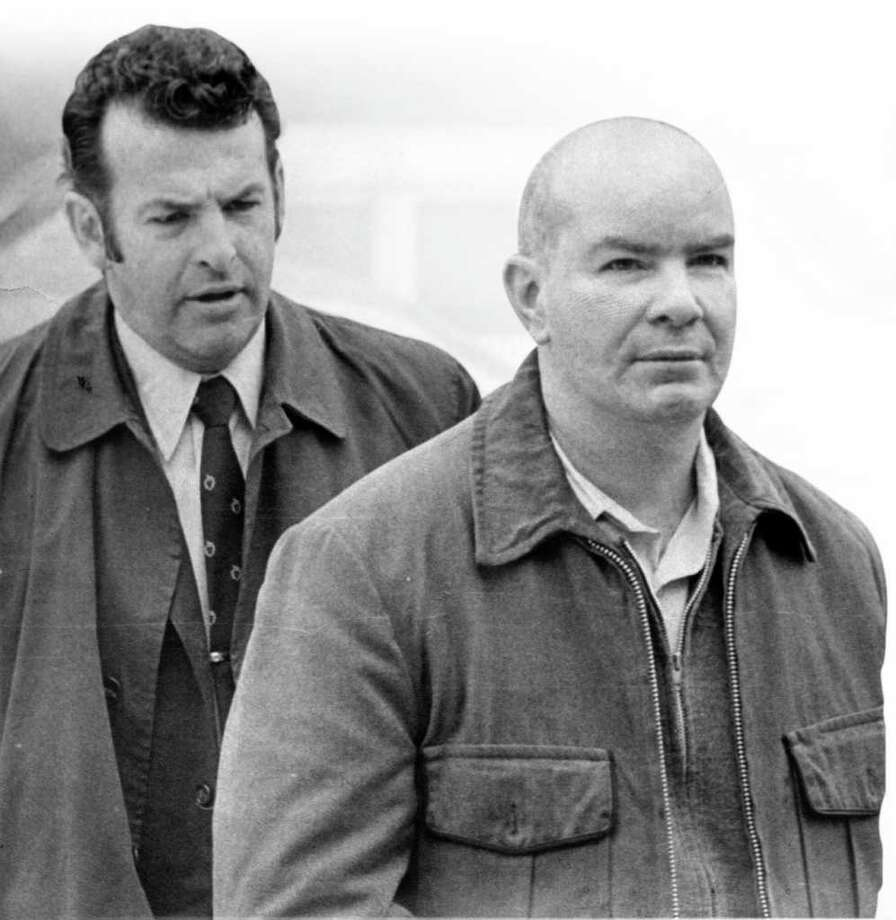 George Mayer, then a Stamford police detective, escorts Ben Miller into police headquarters on March 16, 1972, when Miller was booked on five counts of murder. Photo: File Photo / Stamford Advocate File Photo