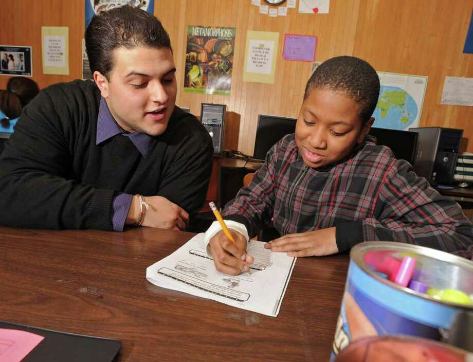 HVCC student Derek Hines helps Jordan Davis, age 11 of Albany, with some homework in an after school program at the State Museum in Albany, NY on January 31, 2011. Hines was part of this program growing up and now mentors kids himself. (Lori Van Buren / Times Union) Photo: Lori Van Buren
