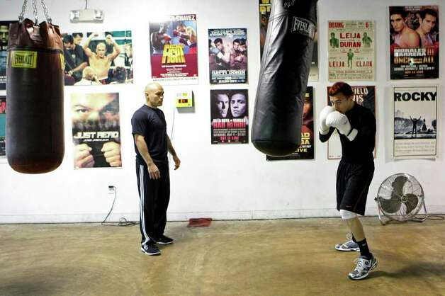 James Leija Jr. (right) trains at ChampionFit Gym as his father watches, with reminders of his father's career lining the walls of the gymnasium. Photo: HELEN L. MONTOYA, Helen L. Montoya/Express-News / hmontoya@express-news.net