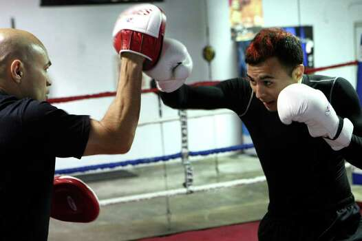 """Jesse"" James Leija (left) trains his son James Leija Jr. on Thursday for his amateur boxing debut tonight at a Golden Gloves regional. Photo: HELEN L. MONTOYA, Helen L. Montoya/Express-News / hmontoya@express-news.net"