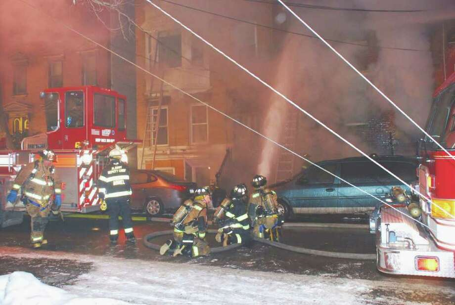 A fire on Grand Street in Albany started shortly before 8 a.m. Monday. Fire officials found a woman's body in the basement after rescuing several people. (Tom Heffernan Sr. / Special to the Times Union)