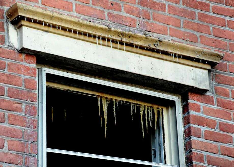 Ice hangs from the window of 71 Grand Street after a two alarm fatal fire consumed 69 Grand Street and spread to the adjacent building in Albany, New York February 22, 2011.    (Skip Dickstein / Times Union) Photo: Skip Dickstein / 2008