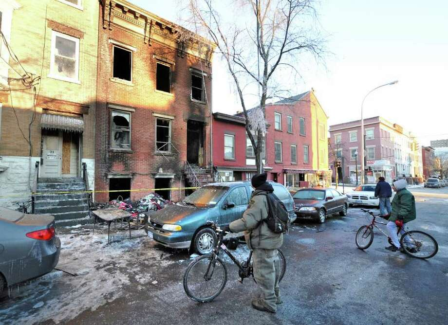 Locals stop by on the way to work to look at the scene of a fatal fire at 69 Grand Street in Albany, New York February 22, 2011.   (Skip Dickstein / Times Union) Photo: Skip Dickstein