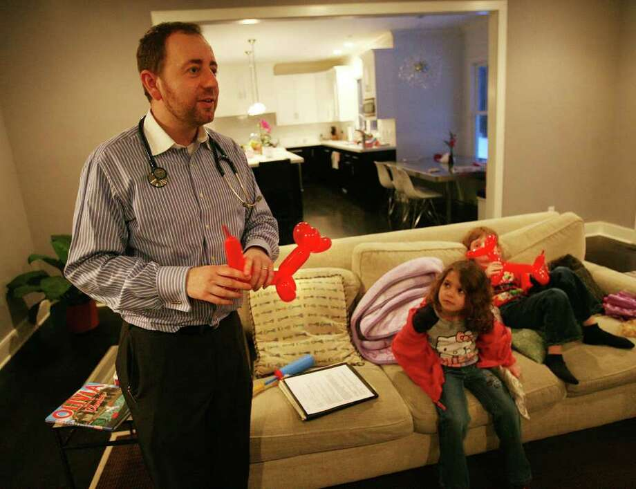 Dr. Edward Kulich of Brooklyn makes balloon animals for patients Genevieve, 5, and Julian Frucht, 7, during a housecall at their Westport home on Sunday, February 13, 2011. Photo: Brian A. Pounds / Connecticut Post