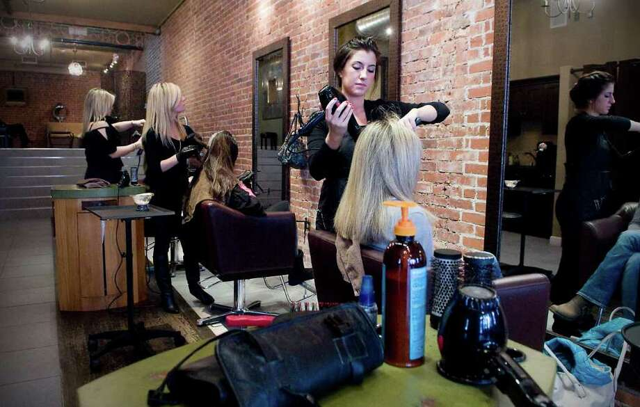 Stylists work on clients at Salon KiKlo, a new salon in New Canaan, Conn. on Thursday February 14, 2011. Photo: Kathleen O'Rourke / Stamford Advocate