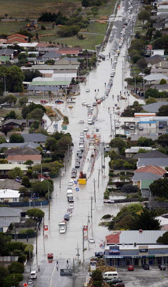 Vehicles move through flooded roads in South Brighton after Christchurch, New Zealand, was hit by a 6.3 magnitude earthquake Tuesday, Feb. 22, 2011. The powerful earthquake struck one of New Zealand's biggest cities Tuesday at the height of a busy workday, toppling tall buildings and churches, crushing buses and killing dozens of people in one of the country's worst natural disasters. (AP Photo/ New Zealand Herald, Sarah Ivey)
