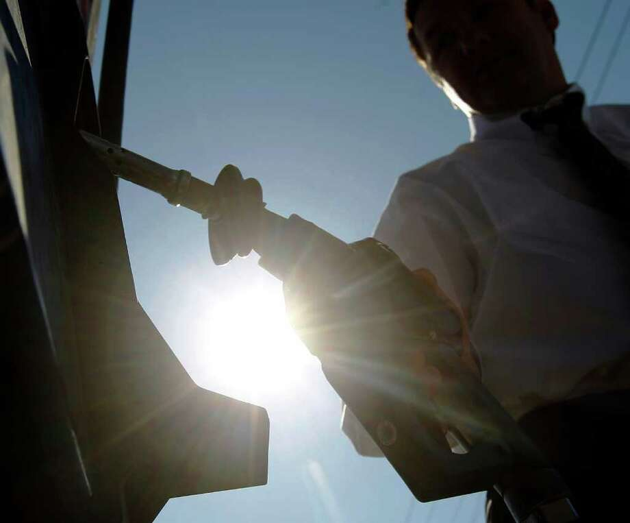 In this Feb. 16, 2011 photo, Brian Sprague returns the nozzle to the pump after filling his car's tank with gas in Philadelphia. Oil prices hovered below $87 a barrel Friday, Feb. 18, as violent protests in the Middle East keep investors on edge about possible crude supply disruptions.(AP Photo/Matt Rourke) Photo: Matt Rourke
