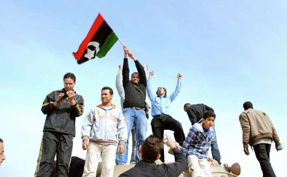 Residents stand on a tank holding a pre-Gadhafi era national flag inside a security forces compound in Benghazi, Libya on Monday, Feb. 21, 2011. Libyan protesters celebrated in the streets of Benghazi on Monday, claiming control of the country's second largest city after bloody fighting, and anti-government unrest spread to the capital with clashes in Tripoli's main square for the first time. (AP Photo/Alaguri) Photo: Alaguri / AP