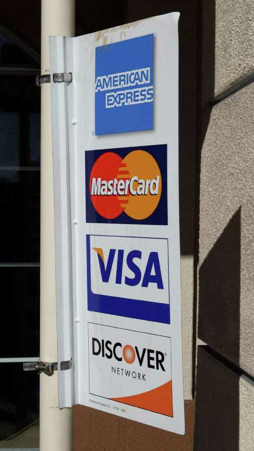 FILE - In this Jan. 18, 2011 file photo, four major credit cards advertise at a restaurant in Millbrae, Calif.  year after sweeping credit card regulations upended the industry, banks are showering perks and rewards on big spenders with sterling credit scores. And they're socking customers with spottier histories with higher interest rates, lower credit limits and new annual fees. In some cases the riskiest customers are being dropped altogether.  (AP Photo/Paul Sakuma, File) Photo: Paul Sakuma