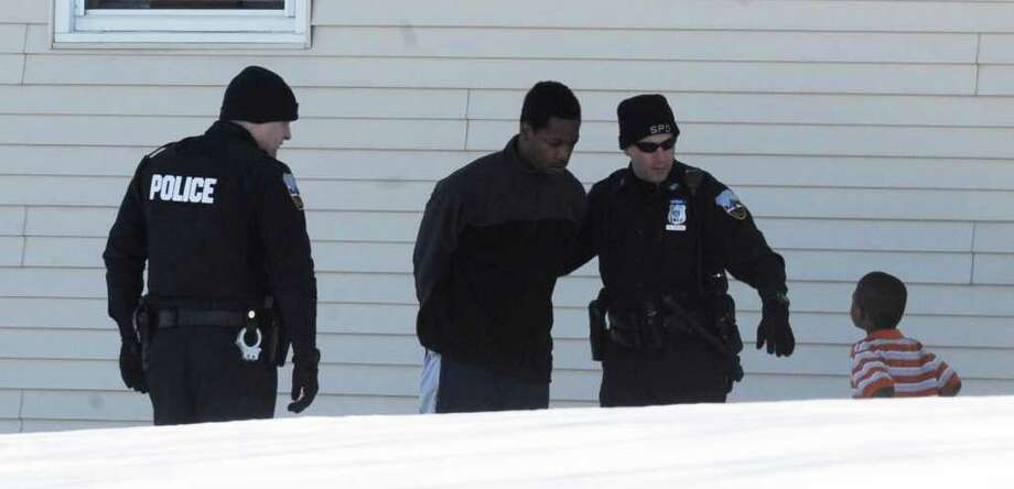 A man is taken in to custody by the Schenectady Police from the rear apartment of 1458 State Street in Schenectady, New York February 22, 2011.  Shortly after the adult was taken in to custody a young child left the building and joined police and was taken to a police cruiser. (Skip Dickstein / Times Union) Photo: SKIP DICKSTEIN / 2008
