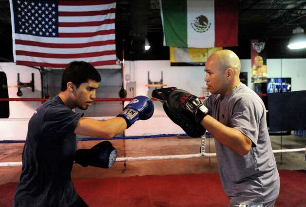 "Boxer Adam Lopez works out with trainer ""Jesse"" James Leija at ChampionFit Gym on Friday, Sept. 24, 2010. Lopez has been boxing since the age of 12. He is attempting to make the U.S. National Boxing team for the 2012 Olympics in London.  BILLY CALZADA / gcalzada@express-news.net Photo: BILLY CALZADA, SAN ANTONIO EXPRESS-NEWS / gcalzada@express-news.net"