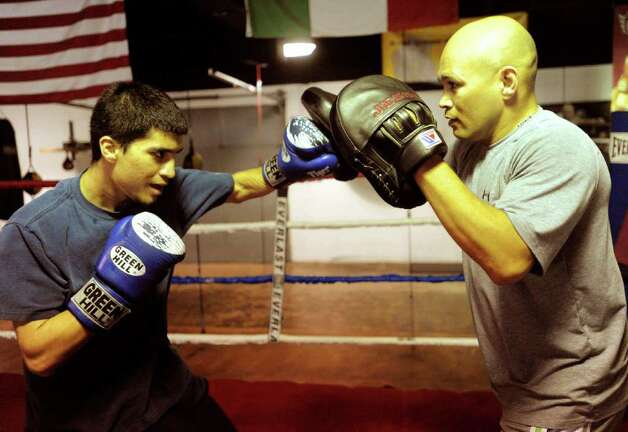 "Boxer Adam Lopez, left, works out with trainer ""Jesse"" James Leija at ChampionFit Gym on Friday, Sept. 24, 2010. Lopez, a six-time national champion boxer, including winning the 2009 National Police Athletic League Boxing Championships in the 114 lbs. open class is attempting to make the U.S. National Boxing team for the 2012 Olympics in London.  BILLY CALZADA / gcalzada@express-news.net Photo: BILLY CALZADA, SAN ANTONIO EXPRESS-NEWS / gcalzada@express-news.net"