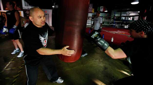 FOR YOUR HEALTH - James Leija moves a punching bag around to help train a gym member at Championfit Gym on Monday, Feb. 8, 2010. MICHAEL MILLER / mmiller@express-news.net Photo: MICHAEL MILLER, SAN ANTONIO EXPRESS-NEWS / mmiller@express-news.net