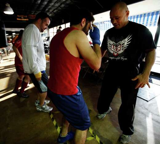 "FOR YOUR HEALTH - James Leija, right, trains members of a ""boot camp""-type fitness class on their footwork at Championfit Gym on Monday, Feb. 8, 2010. MICHAEL MILLER / mmiller@express-news.net Photo: MICHAEL MILLER, SAN ANTONIO EXPRESS-NEWS / mmiller@express-news.net"