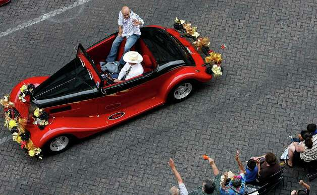 James Leija, grand marshal of the Battle of Flowers parade, waves to the crowd while riding in a vintage Ford automobile on Apr. 24, 2009. Leija is a native San Antonian and former world champion boxer. Leija presides over the oldest and largest parade for Fiesta according to their website. Several hundred thousand spectators were on hand to watch the event despite occasional bouts of rain. Kin Man Hui/kmhui@express-news.net Photo: Kin Man Hui, San Antonio Express-News / San Antonio Express-News