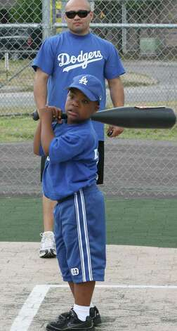 METRO-Damani Green,7, waits for a pitch as Jesse James Lejia plays catcher during league play  for handicapped kids. Jesse James Leija's team, the Leija Dodgers at Mays Family Field of Dreams Saturday June 7,2008. DELCIA LOPEZ/STAFF delopez@express-news.net Photo: DELCIA LOPEZ, SAN ANTONIO EXPRESS-NEWS / delopez@express-news.net