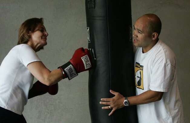 "SPORTS - ""Jesse"" James Leija works out with Carole Palmer on the punching bag at his gym on Thursday, April 20, 2006. Since retiring from the boxing profession, Leija, continues to stay busy with his gym operation amongst his other enterprises. (Kin Man Hui/staff) Photo: KIN MAN HUI, SAN ANTONIO EXPRESS-NEWS / SAN ANTONIO EXPRESS-NEWS"