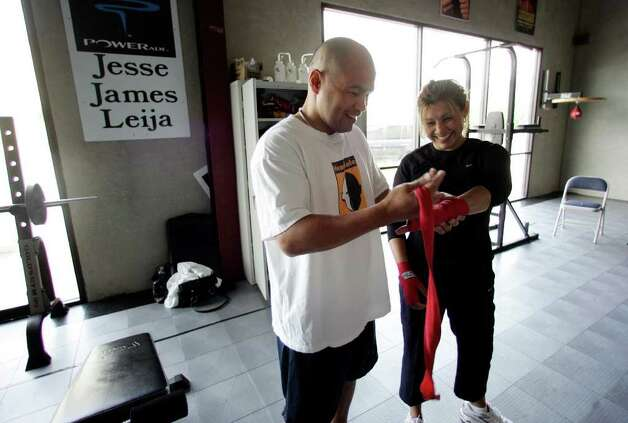"SPORTS - Local boxing icon ""Jesse"" James Leija (left) wraps the hands of his wife, Lisa, at his gym on Thursday, April 20, 2006. Since retiring from the boxing ring, Leija has operated a boxing gym that caters to anyone interested in the sport and in fitness. One of Leija's exercise programs focuses on women's fitness which his wife, Lisa, participates. (Kin Man Hui/staff) Photo: KIN MAN HUI, SAN ANTONIO EXPRESS-NEWS / SAN ANTONIO EXPRESS-NEWS"