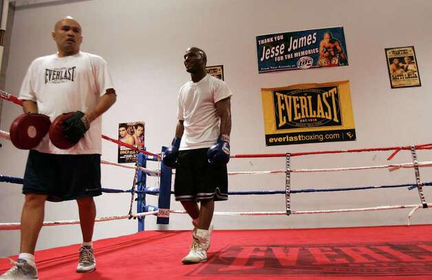 "SPORTS - Local boxing legend ""Jesse"" James Leija finishes a training session with a smiling welterweight boxer Golden Johnson Leija's gym on Wednesday, Feb. 15, 2006. Since Johnson's appearance on reality television show, The Contender, he has worked to make a comeback, of sorts, after he injured his right wrist forcing him to exit early from the show. Leija is now managing and training him for a professional bout. (Kin Man Hui/staff) Photo: KIN MAN HUI, SAN ANTONIO EXPRESS-NEWS / SAN ANTONIO EXPRESS-NEWS"