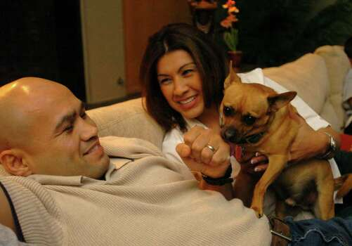 "SPORTS - ""Jesse"" James Leija and his wife, Lisa, enjoy a moment with one of the family's dogs in their San Antonio home on Wednesday, Feb. 2, 2005. BILLY CALZADA / STAFF Photo: BILLY CALZADA, SAN ANTONIO EXPRESS-NEWS / SAN ANTONIO EXPRESS-NEWS"