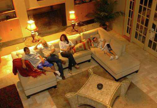 "SPORTS - Boxer ""Jesse"" James Leija and his wife, Lisa, sit with their children, James, left, and Dean, right, in their San Antonio home on Wednesday night, Feb. 2, 2005. They were watching ""American Idol"" on television. BILLY CALZADA / STAFF Photo: BILLY CALZADA, SAN ANTONIO EXPRESS-NEWS / SAN ANTONIO EXPRESS-NEWS"
