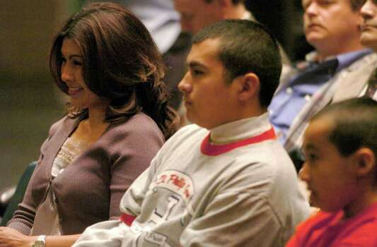 SPORTS - Lisa Leija and her sons, James and Dean, right, listen as their husband and father, 'Jesse' James Leija, announces his retirement from professional boxing during a press conference at Municipal Auditorium on Thursday, Feb. 3, 2005.  BILLY CALZADA / STAFF Photo: BILLY CALZADA, SAN ANTONIO EXPRESS-NEWS / SAN ANTONIO EXPRESS-NEWS