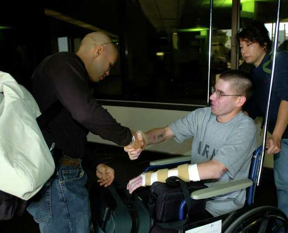 SPORTS - San Antonio boxer Jesse James Leija greets U.S. Army Spc. Sean Beveridge, who was wounded in a suicide bombing in Iraq, at San Antonio International Airport on Tuesday, Jan. 25, 2005. Leija was on his way to Atlantic City, where he will face Arturo Gatti in a championship match. Beveridge was on his way home to Duvall, Wash. BILLY CALZADA / STAFF Photo: BILLY CALZADA, SAN ANTONIO EXPRESS-NEWS / SAN ANTONIO EXPRESS-NEWS