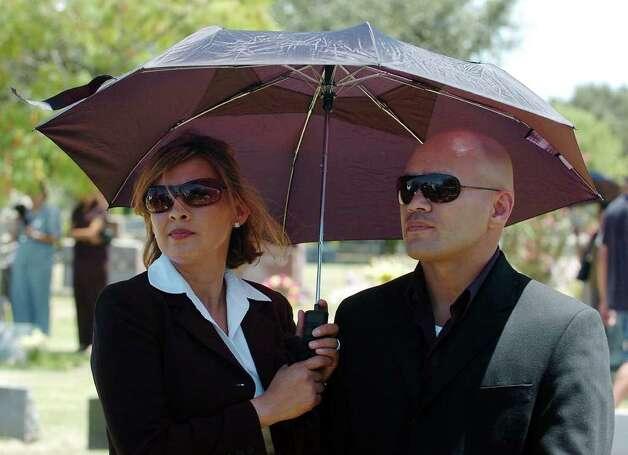 METRO - James Leija (right) and his wife, Lisa, attend the graveside service for Robert Quiroga on Friday, Aug. 20, 2004. Leija was one of many boxers who attended the service to honor the former world champion fighter. (Kin Man Hui/staff) Photo: KIN MAN HUI, SAN ANTONIO EXPRESS-NEWS / SAN ANTONIO EXPRESS-NEWS