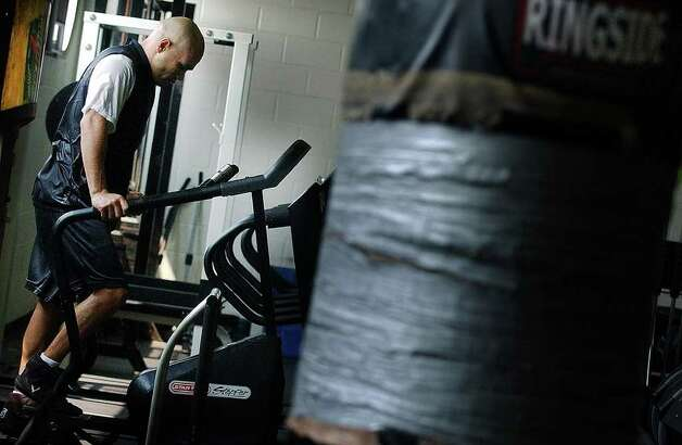 "SPORTS - Jesse ""James"" Leija works up a sweat on a stair-climbing machine at the Atlantic City Polica Athletic League gym in Atlantic City on Thursday, July 22, 2004. Leija will face off against up-and-comer Francisco Bojado in a junior welter-weight fight on Saturday. Leija has a 16-year career in boxing that has earned him a title along with millions in prize money. (Kin Man Hui/staff) Photo: KIN MAN HUI, SAN ANTONIO EXPRESS-NEWS / SAN ANTONIO EXPRESS-NEWS"