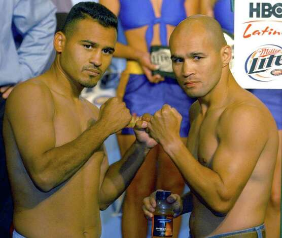 Boxers Adan Casillas (L) and James Leija (Rt.) pose during a weigh in Wednesday May 21 , 2003 , at Dave and Buster's prior to their bout at the SBC Center Thursday night. Leija weighed in at 141 pounds and Casillas weighed in at 139 1/2 pounds. JOHN DAVENPORT /STAFF Photo: JOHN DAVENPORT, SAN ANTONIO EXPRESS-NEWS / SAN ANTONIO EXPRESS-NEWS