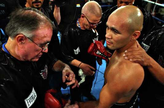 "Jesse James Leija, left, takes off the gloves after beating Fernado Mena during round two of the ""Clash of the Titans"" main event Saturday, November 15, 2003 at the Alamodome in San Antonio, Texas. NICOLE FRUGE/SAN ANTONIO EXPRESS-NEWS Photo: Nicole Fruge, San Antonio Express-News / San Antonio Express-News"