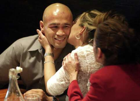 "SPORTS   ---   Lisa Leija kisses her husband ""Jesse"" James Leija during a post-fight dinner Sunday night Jan. 19, 2003 in Melbourne, Australia after Leija lost his fight against world title holder Kostya Tszyu at the Telstra Dome. Leija's mother is at right in red.   (WILLIAM LUTHER/STAFF) Photo: WILLIAM LUTHER, SAN ANTONIO EXPRESS-NEWS / SAN ANTONIO EXPRESS-NEWS"
