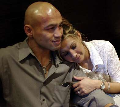 "SPORTS   ---   Lisa Leija hugs her husband""Jesse"" James Leija during a post-fight dinner Sunday night Jan. 19, 2003 in Melbourne, Australia after losing his fight against world title holder Kostya Tszyu at the Telstra Dome.   (WILLIAM LUTHER/STAFF) Photo: WILLIAM LUTHER, SAN ANTONIO EXPRESS-NEWS / SAN ANTONIO EXPRESS-NEWS"