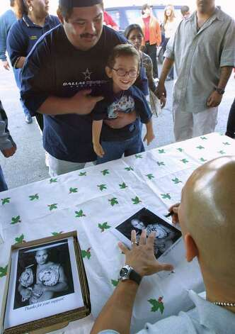 METRO / SPORTS, JAMES LEIJA; 12/15/02; Jesse James Leija, right, meets fans and signs autographs for them at the S.W. Military Drive Sam's Club Sunday afternoon. Here, three-year-old Leonardo Charles gets a boost from his dad, Leonardo Charles, Jr., to ask Leija for an autograph. Fans also had the opportunity to sign a 12' x 20' banner, wishing Leija luck in bringing home another world title. The banner will travel with him to his world titlebout in Australia on Jan. 18, 2003. ( PHOTO BY J. MICHAEL SHORT / SPECIAL ) Photo: J. MICHAEL SHORT, SPECIAL TO THE EXPRESS-NEWS / SAN ANTONIO EXPRESS-NEWS