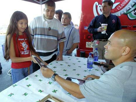 METRO / SPORTS, JAMES LEIJA; 12/15/02; Jesse James Leija meets fans and signs autographs for them at the S.W. Military Drive Sam's Club Sunday afternoon. Here, Leija, right, hands an autographed photo of himself to a slightly bashful Amanda Flores, left, as her older brother Rene Flores, second from left, waits for his photo. Fans also had the opportunity to sign a 12' x 20' banner, wishing Leija luck in bringing home another world title. The banner will travel with him to his world titlebout in Australia on Jan. 18, 2003. ( PHOTO BY J. MICHAEL SHORT / SPECIAL ) Photo: J. MICHAEL SHORT, SPECIAL TO THE EXPRESS-NEWS / SAN ANTONIO EXPRESS-NEWS