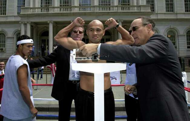 "FOR SPORTS DAILY - Jesse James Leija(center) flexes his muscles while New York City Mayor Rudolph W. Giuliani (right)checks his weight as Hector ""Macho"" Camacho, Jr. (left) looks on outside City Hall in New York, NY Friday July 6, 2001 during a weigh-in. Leija is scheduled to fight Hector ""Macho"" Camacho, Jr. Saturday July 7, 2001 at KeySpan Park in Coney Island, Brooklyn, NY in a 10 Round Super Lightweight Bout. PHOTO BY EDWARD A. ORNELAS/STAFF Photo: EDWARD A. ORNELAS, EN / EN"