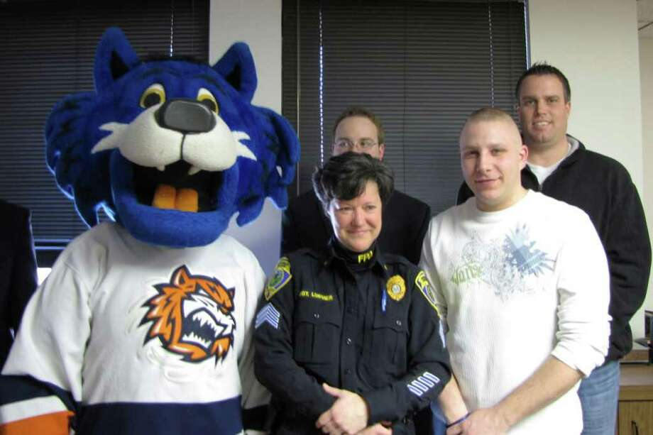 Standing from left to right are Storm, the mascot of the Bridgeport Sound Tigers, Sgt. Suzanne Lussier, spokesperson for the Fairfield Police and a driving force behind the department's  K-9 fundraising campaign, Sound Tigers representative Daniel Travis (hidden behind Lussier), and Officer Michael Paris, who is standing in front of Officer Kevin Wells. All were present Tuesday for a press conference announcing a March K-9 Unit fundraiser that will take place at the Sound Tigers' Webster Bank Arena.  Paris and Wells are two of eight in the running to become the police department's K-9 handler. Photo: Kirk Lang / Fairfield Citizen