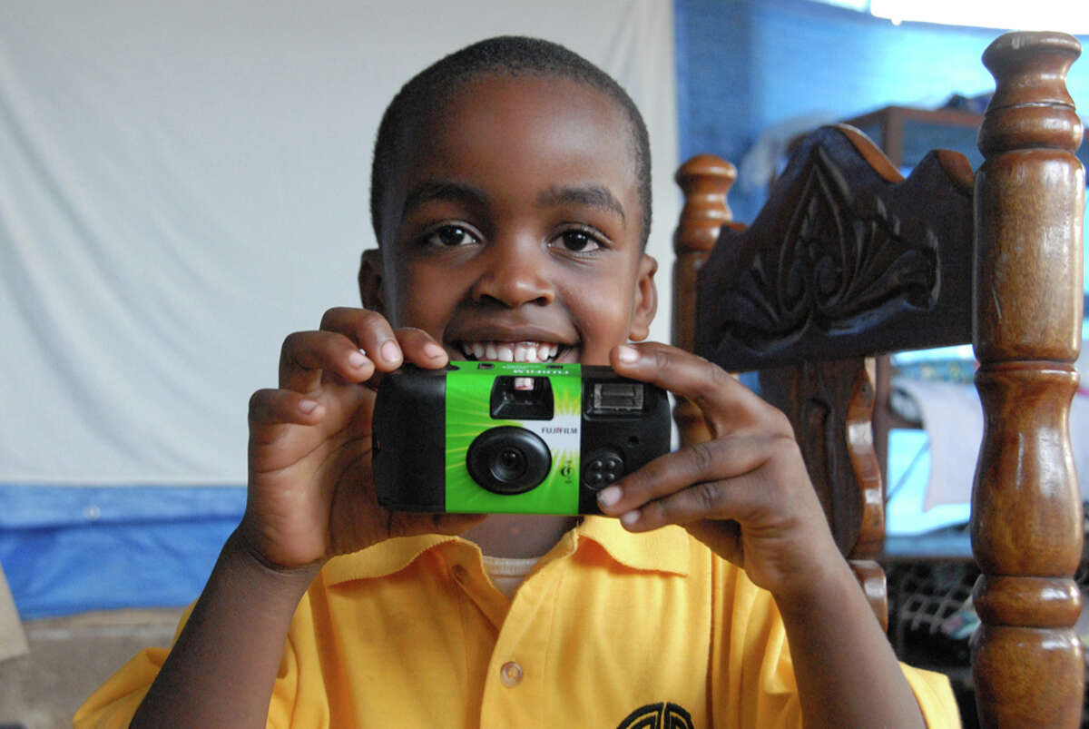In this photo by Helen Klisser During, an orphan from Carma House, Haiti poses with his Fujifilm disposable camera. The photographs of approxamately 50 Haitian orphans will be part of