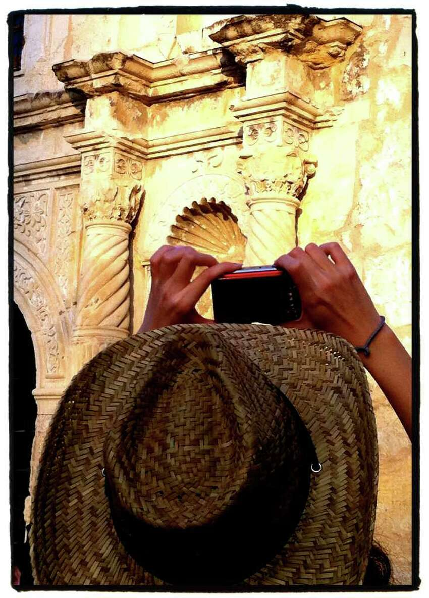 A visitor takes a snapshot during a tour of the Alamo.