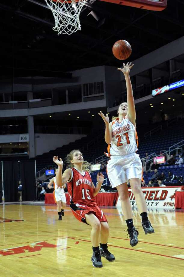 Ridgefield's Gemma Howard takes a shot as she is guarded by New Canaan's Hannah Femia during Tuesday's FCIAC girls basketball semifinal game at the Webster Bank Arena at Harbor Yard on Feburary 22, 2011. Photo: Lindsay Niegelberg / Connecticut Post
