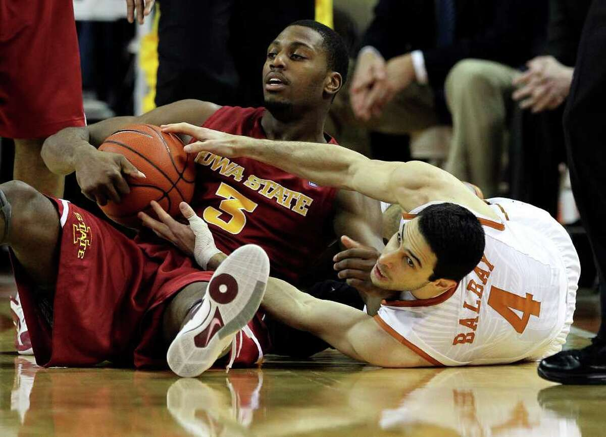 Texas Longhorns' Dogus Balbay (04) struggles for a loose ball against Iowa State's Melvin Ejim (03) in the first half in men's basektball in Austin on Tuesday, Feb. 22, 2011. Kin Man Hui/kmhui@express-news.net