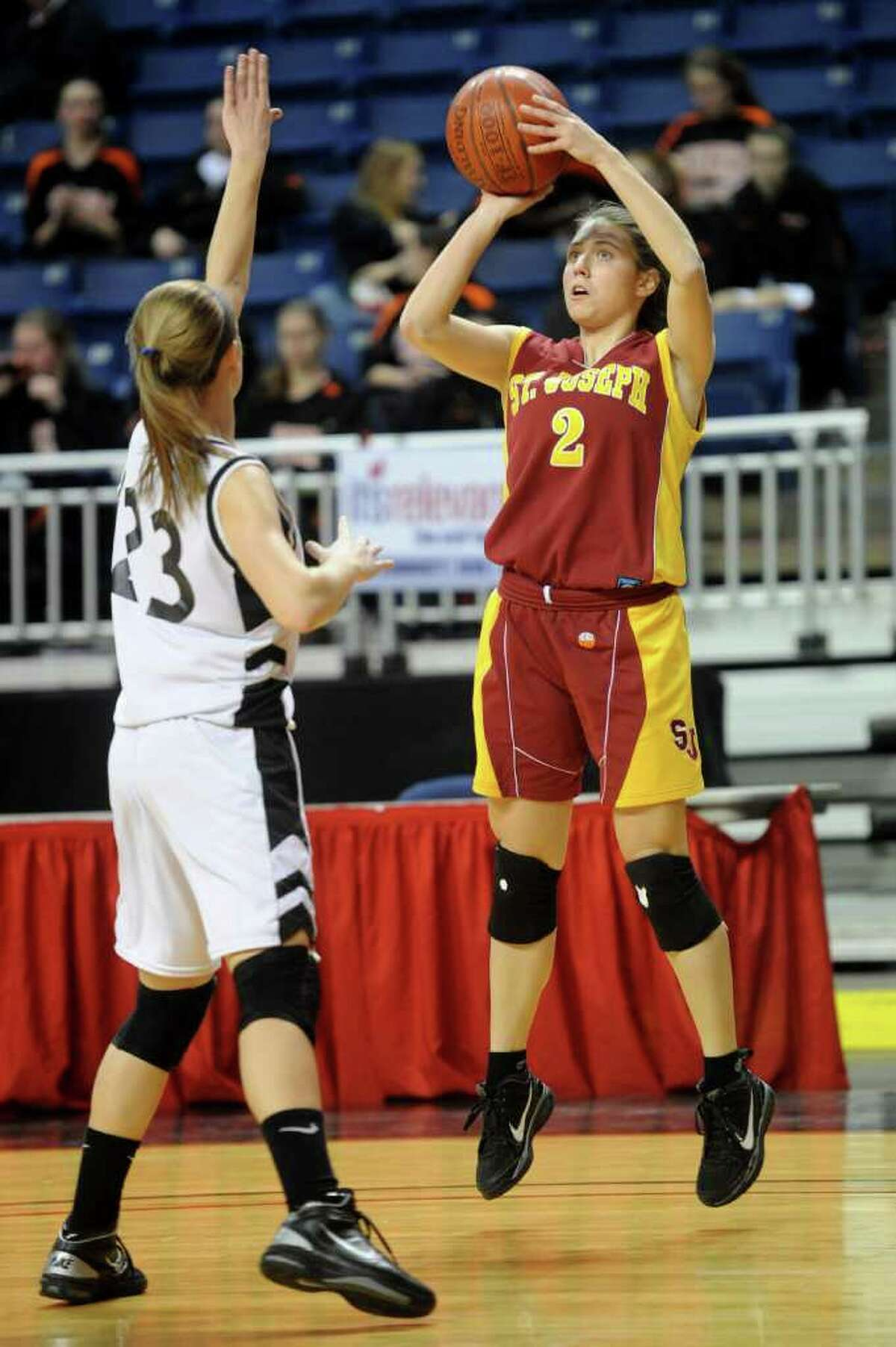 Jessica Jowdy of St. Joseph takes a shot as she is guarded by Trumbull's Victoria Pfohl during Tuesday's FCIAC girls basketball semifinal game at the Webster Bank Arena at Harbor Yard on Feburary 22, 2011.
