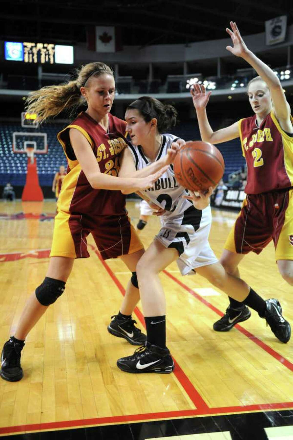 Trumbull's Kelly Coughlin, center, tries to hold onto the ball as she is surrounded by St. Joseph's Taylor Whiting, left, and Nancy Stablein, right, during Tuesday's FCIAC girls basketball semifinal game at the Webster Bank Arena at Harbor Yard on Feburary 22, 2011.