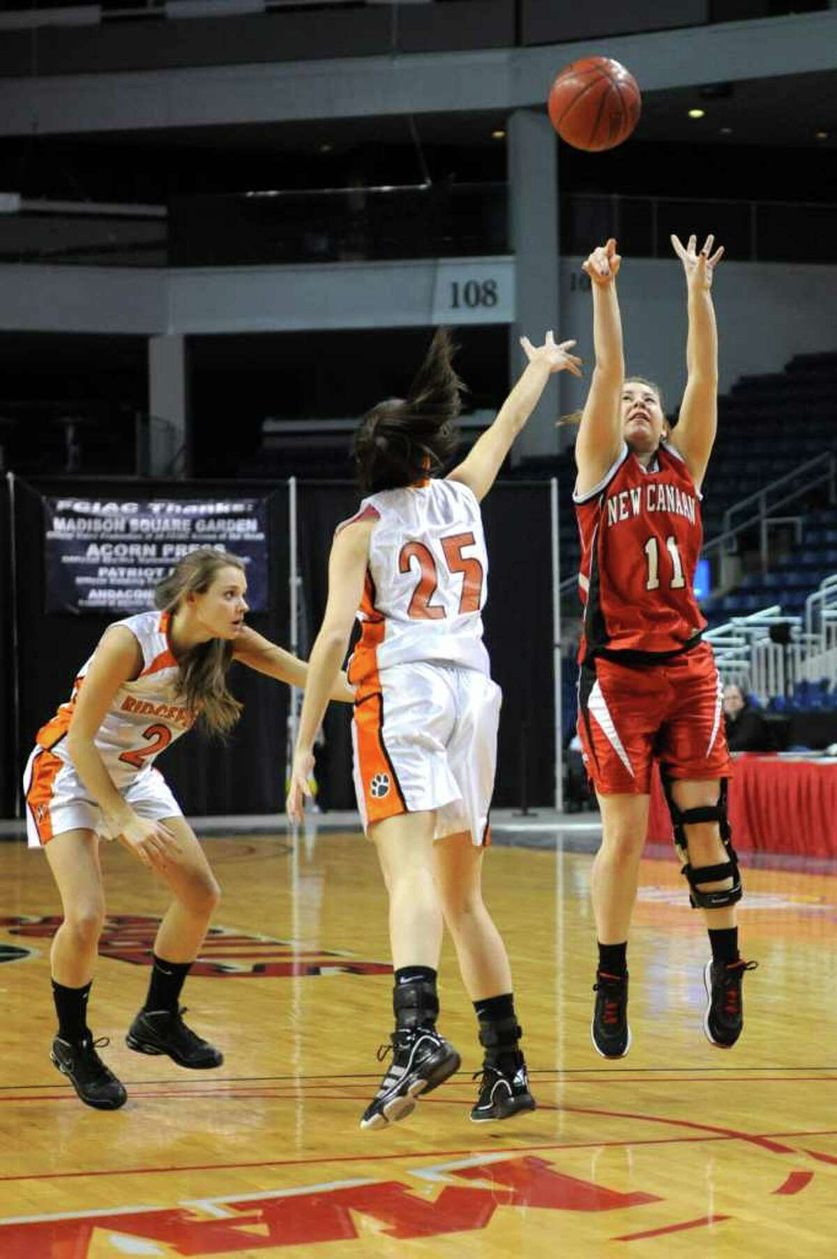 New Canaan's Courtney Rogers takes a shot as Ridgefield's Molly Welch, center, and Lauren Eckstrom, left, defend during Tuesday's FCIAC girls basketball semifinal game at the Webster Bank Arena at Harbor Yard on Feburary 22, 2011.