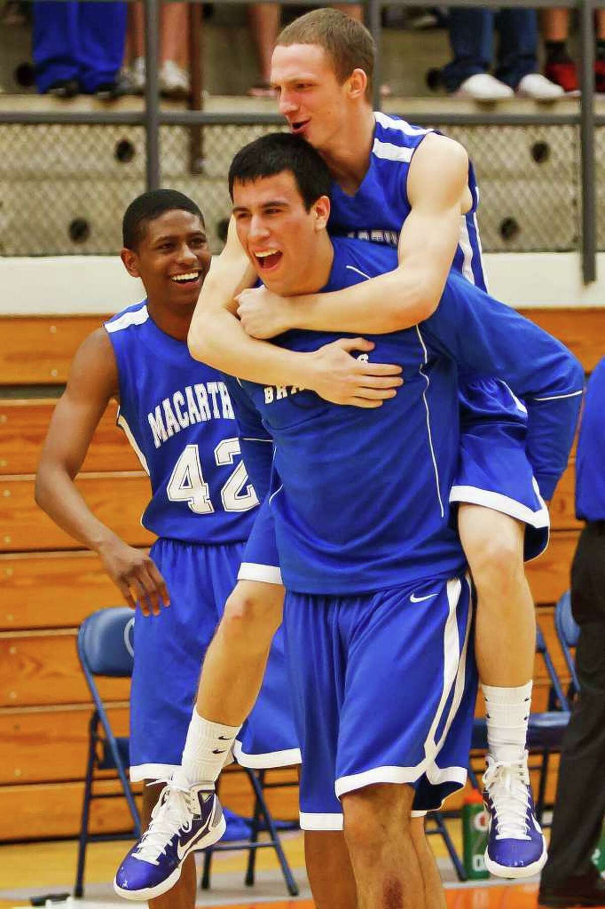 MacArthur's Jon Kaster jumps on the back of Jace Amaro as Alonzo Lewis looks on after the Brahmas' 56-54 second-round overtime victory over Judson at Paul Taylor Field House on Tuesday, Feb. 22, 2011.