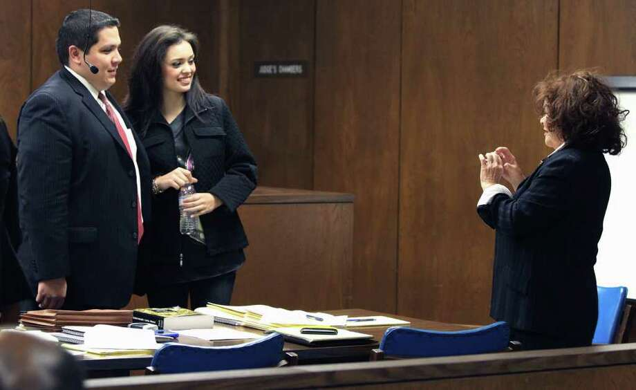 Domonique Ramirez (center) poses for a picture during a trial break in the 224th District Court on Feb. 22. Ramirez's title of Miss San Antonio 2011 was taken away by the Miss Bexar County Organization, Inc. and now Ramirez is suing. A counterclaim filed by the Miss Bexar County Organization accuses Ramirez and her mother of breach of contract. Photo: JOHN DAVENPORT / jdavenport@express-news.net