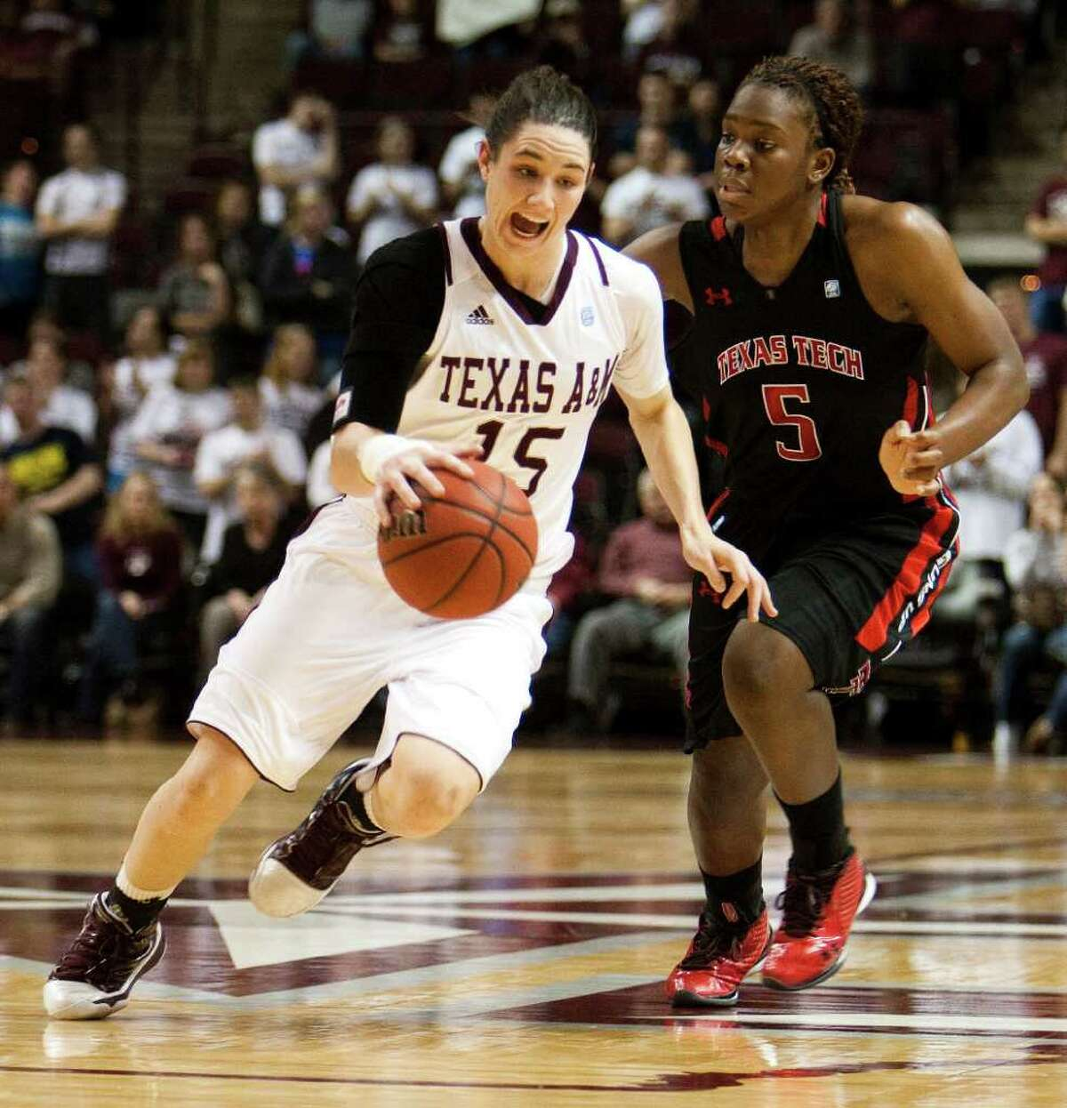Texas A&M guard Maryann Baker (15) drives the ball against Texas Tech's Christina Hyde (5) during the first half of an NCAA college basketball game Tuesday, Feb. 22, 2011, in College Station, Texas.