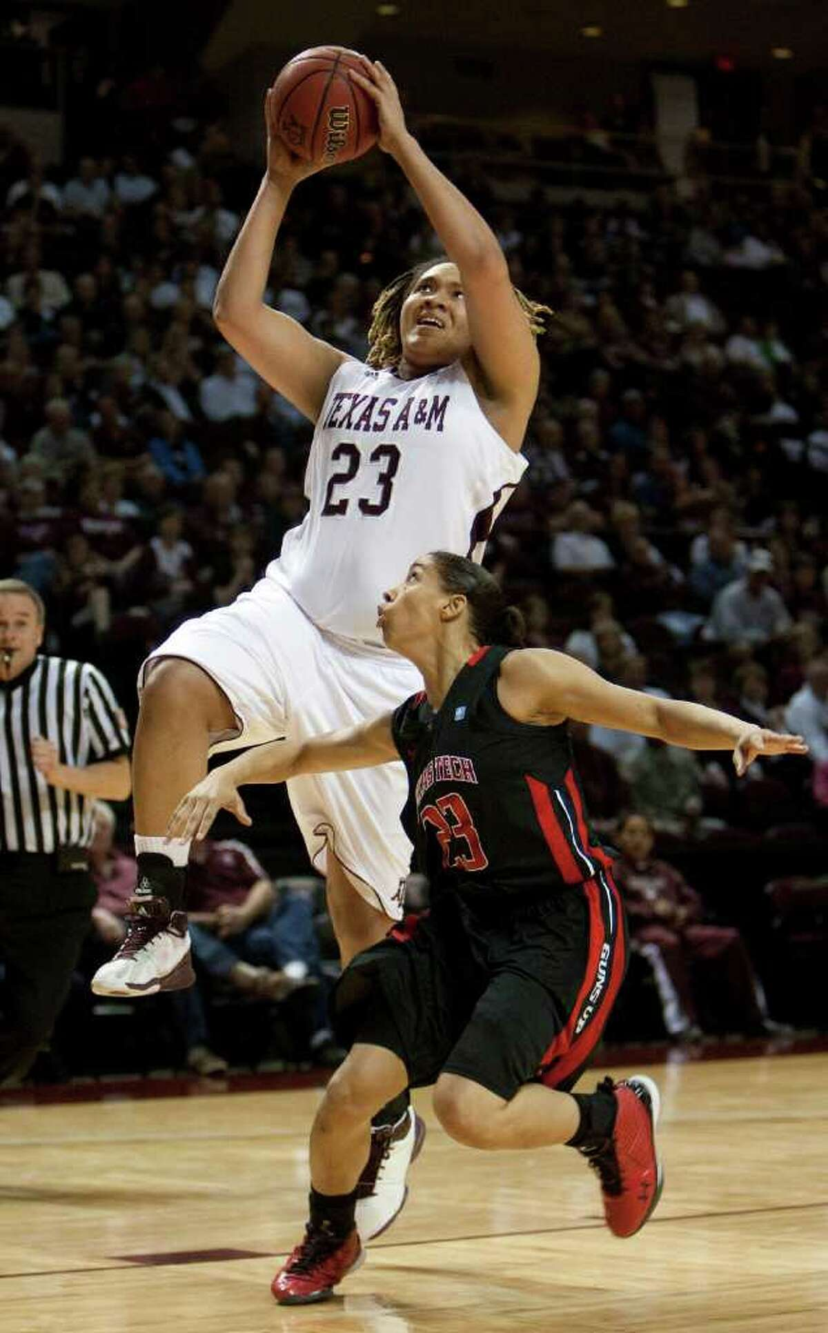 Texas A&M's Danielle Adams (23) goes to the basket over Texas Tech defender Monique Smalls (23) during the first half of an NCAA college basketball game Tuesday, Feb. 22, 2011, in College Station, Texas.